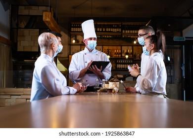 der Küchenchef führt eine Besprechung der Mitarbeiter im Restaurant durch