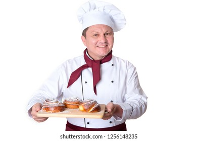 Chef confectioner holds on a tray fresh buns on a white background. Male cook.