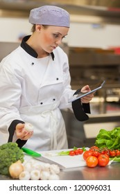Chef consulting digital tablet before preparing vegetables in the kitchen