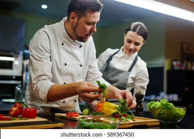 Chef consulting his trainee while cooking salad