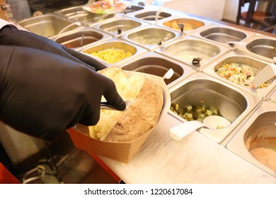 Chef cook in black gloves is making Kumpir - Turkish traditional meal with baked potato, butter, cheese, and vegetables in Restaurant.