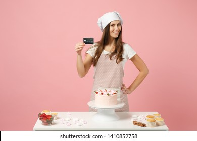 Chef cook confectioner or baker in apron white t-shirt, toque chefs hat cooking cake or cupcake at table hold credit card isolated on pink pastel background in studio. Mock up copy space food concept