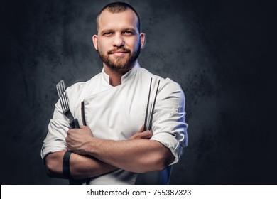 Koch-Koch hält ein Messer auf dunkelgrauem Hintergrund.