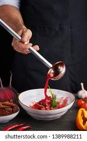 chef cook pours red soup borsch by ladle. Ukrainian and russian cuisine concept. vertical. Copy space