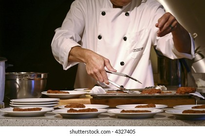 A chef or cook is preparing multiple dishes.
