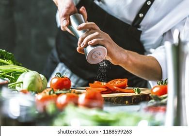 Chef cook preparing vegetables in his kitchen. - Shutterstock ID 1188599263
