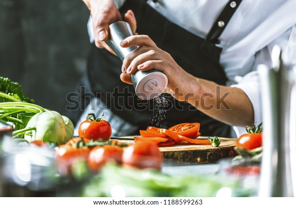 Chef cook preparing vegetables in his kitchen.