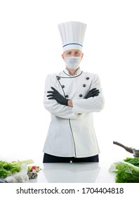 Chef cook in protective medical mask near the kitchen table. Safety and pandemic concept