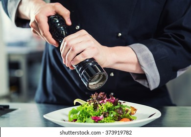 Chef cook in restaurant kitchen peppering salad, crop on hands, filtered image