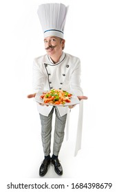 Chef cook in white uniform holds a plate with a shrimps pasta on a white background