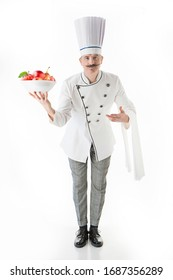 Chef cook in white uniform holds a plate with a apples on a white background