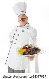 Chef cook in white uniform with a plate with beef steak and vegetables on a white background