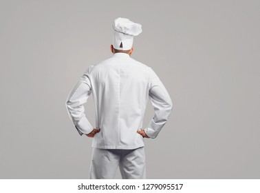 Chef cook in white uniform standing back view .