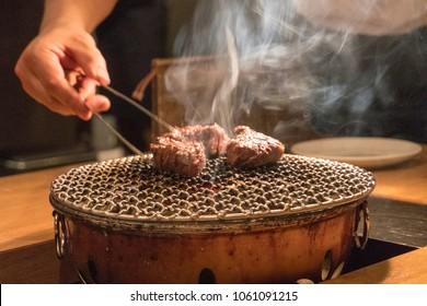 Chef cooking beef steak in Japanese Teppanyaki style. Grilled wagyu Sirloin meat yakiniku. Wagyu Japanese raw beef thick slice steak on grill.