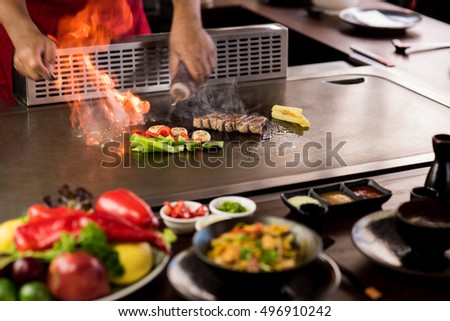 Chef cooking beef teppanyaki on a hot plate