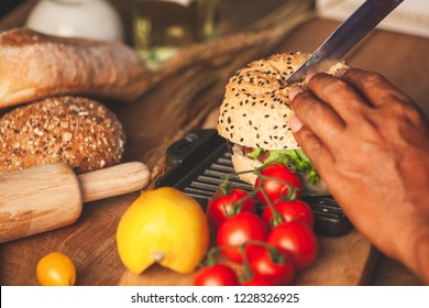 Chef cooking and cutting delicious homemade hamburger with fresh vegetables in the kitchen