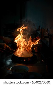 Chef cooking and doing flambe on food in restaurant kitchen