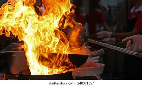 Chef Cooking With Fire In Frying Pan. Professional chef in a commercial kitchen cooking flambe style. Chef frying food in flaming pan on gas hob in commercial kitchen.