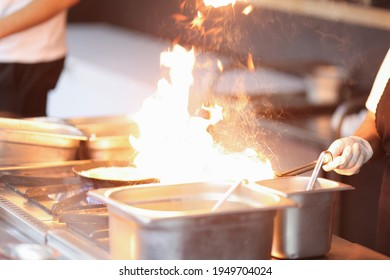 Chef cooking flambe on food in restaurant kitchen closeup