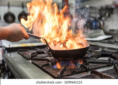 Chef cooking with flame in a frying pan on a kitchen stove.