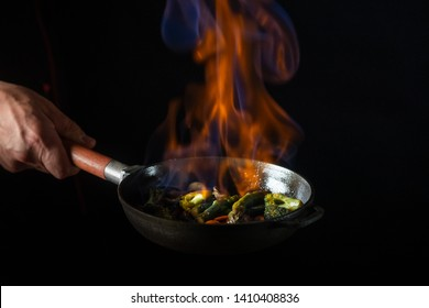 Chef cooking food in pan with fire flame on black background. Restaurant and hotel service concept.