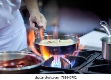 Chef cooking in kitchen, chef preparing food, Chef at work on restaurant kitchen