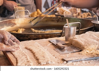 Chef cooking and prepare raw dough for the traditional thai street food dessert - deep fried dough sticks. Thai donuts. Selected focus