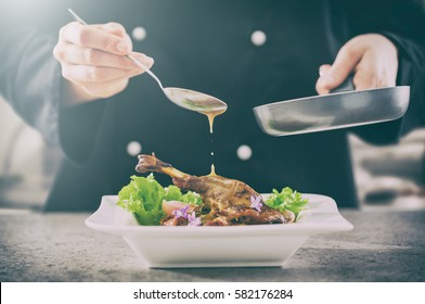 chef cooking restaurant food salad sauce gourmet molecular decorating kitchen dish garnish plate serving lunch top dinner concept - stock image