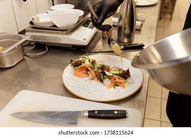 Der Chefkoch kocht Lachsalat in einer kommerziellen Küche