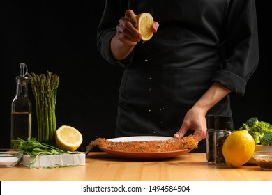 Chef cooking seafood, red fish pouring lemon, salmon or trout on a black background. Movement, restaurant menu, recipe book, Asian cuisine, homemade recipe. Square photo