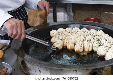 Chef cooking Shanghai pan fried pork dumpling