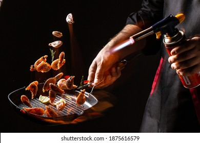 Chef cooking shrimp in pan with fire flame. Culinary seafood and food on a dark background.. Restaurant and hotel service concept.