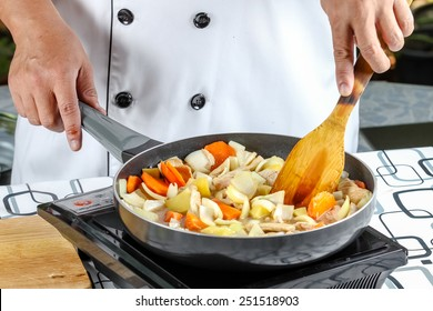 chef cooking stir fry vegetables with pork in outdoor kitchen