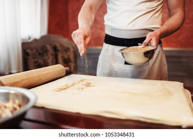 Chef cooking strudel, ingredients on background