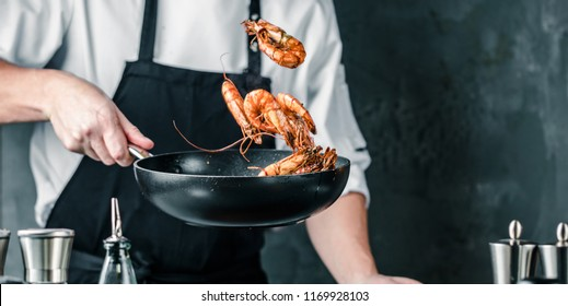 Chef cooking with Tiger prawn on dark background