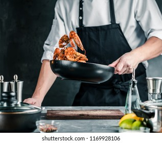 Chef cooking with Tiger prawn on dark background