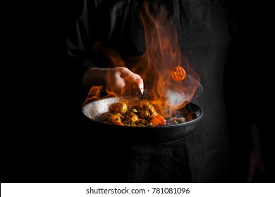 Chef cooking vegetables on a pan with fire flambe. Black background for copy text.