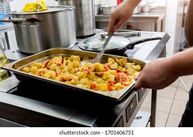 Chef cooks fried potatoes with pieces of meat in a restaurant kitchen