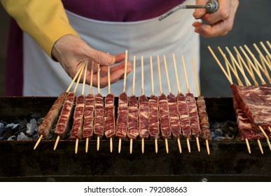 chef cooks meat of lamb called Arrosticini in italian language. They are a class of traditional italian cuisine of Abruzzo Region