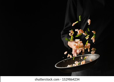 Chef cooks shrimps with green herbs in a pan on a black background. Seafood and healthy food.