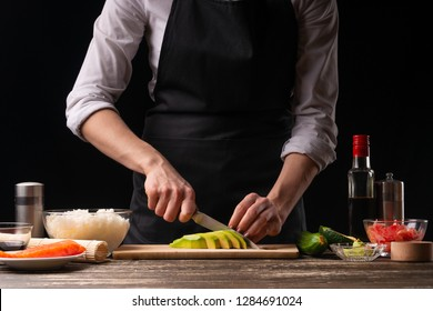The chef cuts avocados for cooking Japanese sushi, rolls. The concept of delicious Japanese food, cooking, gastronomy, menus and recipe books
