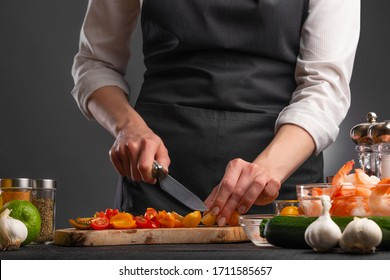 The chef cuts cherry tomatoes to make a fresh salad with shrimp, seafood. Cookery and recipe book. Restaurant cuisine. Recipes