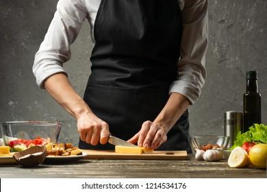 Chef cuts mozzarella cheese for pasta. Pizza, salad, Italian culinary recipe concept, on the background of a concrete wall