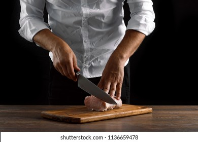 The chef cuts a piece of fresh meat on a wooden board against a dark background, hands close-up. The concept of cooking, cooking meat, a recipe for meat dishes.