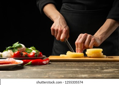 The chef cuts the pineapple. For the preparation of pizza, salad. The concept of delicious food and healthy food. On a black background for design or lettering text. Close-up