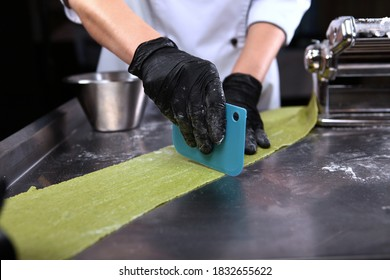 The chef cuts the prepared pasta dough into portions. Homemade dough with spinach. Unrecognizable person. Hands in protective black gloves.Machine for preparing pasta or a pasta machine. Top view.