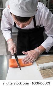 Chef cuts salmon or trout when preparing philadelphia sushi rolls.