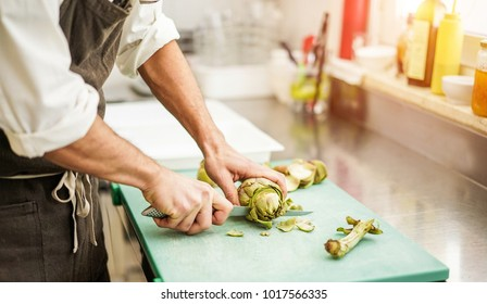 Chef cutting artichokes for dinner preparation - Man cooking inside restaurant kitchen - Focus on vegetable - Vegan cuisine, lifestyle and healthy food concept
