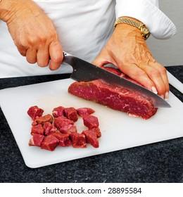 Chef cutting beef