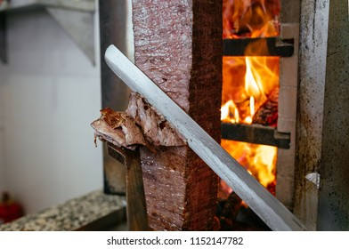 Chef cutting with doner knife Traditional Turkish Doner Kebab meat. shawarma or gyros. Turkish, greek or middle eastern arab style doner kebab food spit in front of grill.